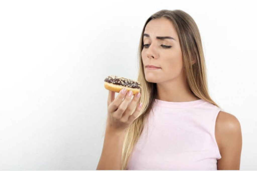 a girl thinking of eating a donut